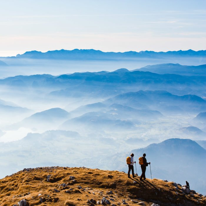Hikers in Slovenian Alps with Lake Bled in the distance