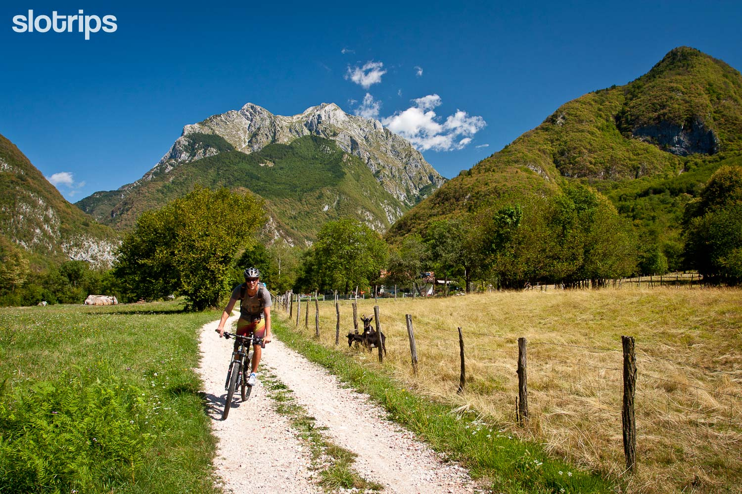 Biker in the Soca valley with rugged mountains in the background