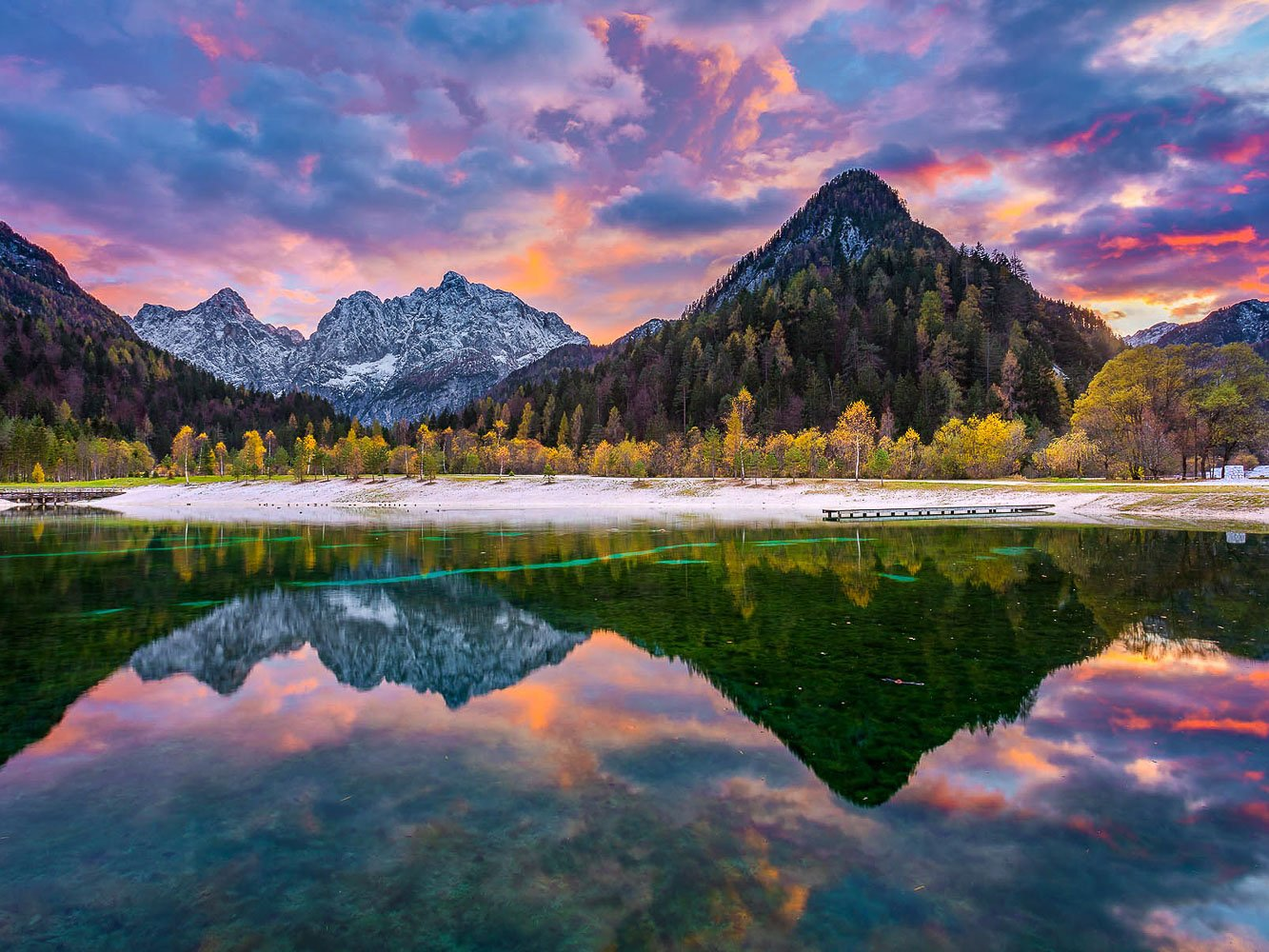 Fantastic colorful caption of autumn nature with mountains and sunset skies mirroring in the Lake Jasna on a photography day trip near Kranjska Gora.
