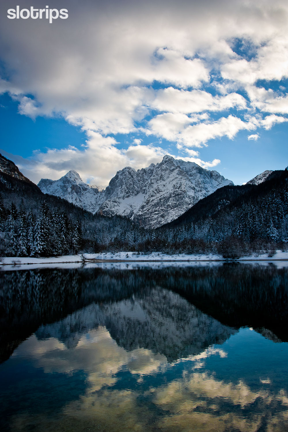 Winter hiking trip at Lake Jasna near Kranjska Gora with Julian Alps reflection.
