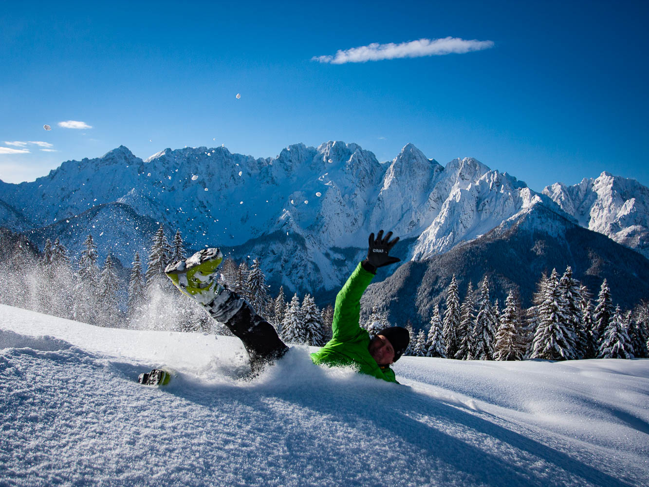 Back country skier joyfully throws himself in deep powder snow backed with a beautiful snow covered mountain panorama of Julian Alps.