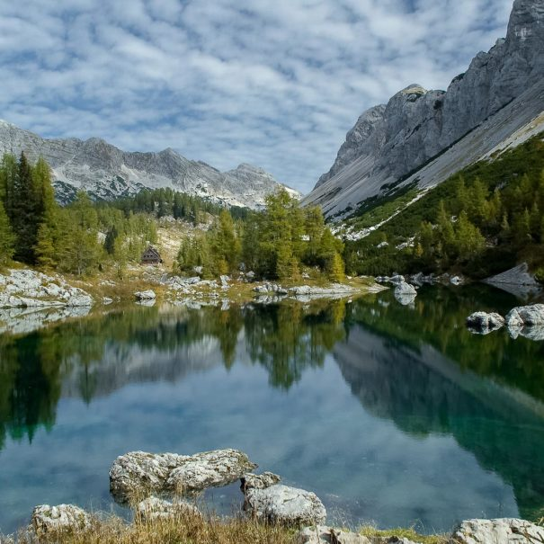 Beautiful deep green Double Lake reflecting mountains and forests above the Seven Triglav Lakes mountain hut.