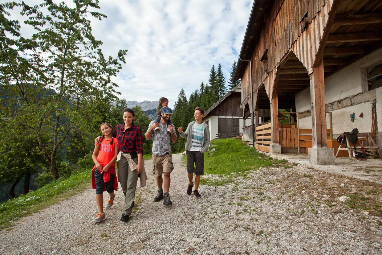 Happy family with kids on a casual walk on a farm while on hiking holidays in Slovenia.