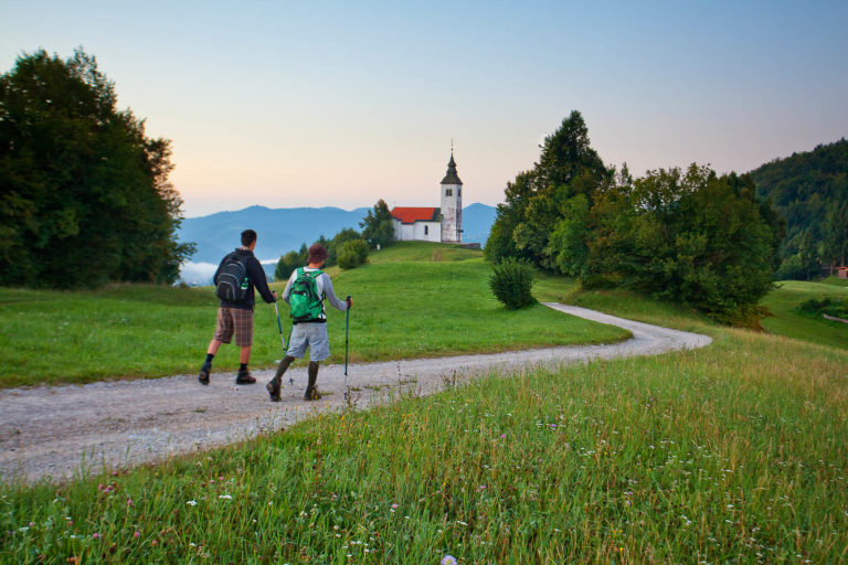 Father and son on a hiking trip in the Skofja Loka hills, walking along the winding gravel road to a hilltop church amid the green meadows.