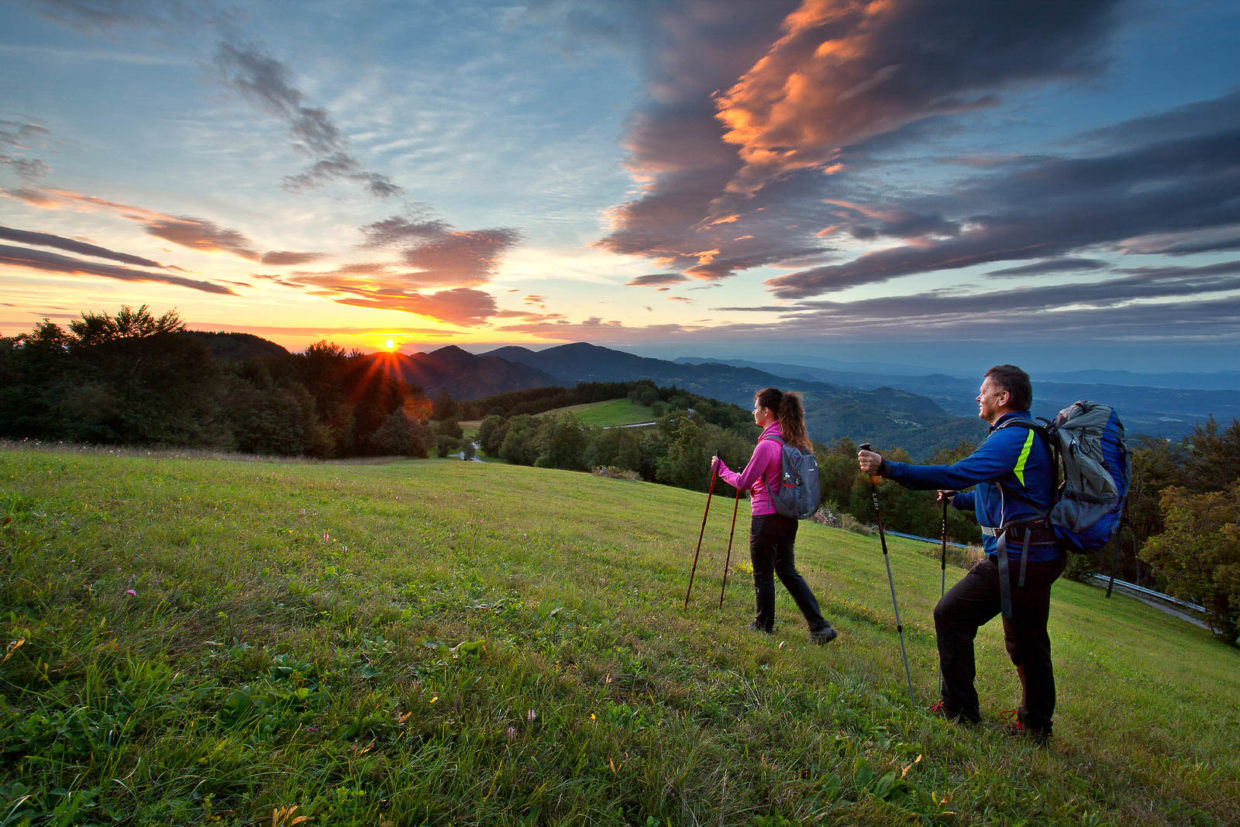 Hikers walking across the green meadows of Lisca hiking trail in Posavje region with a beautiful sunset.