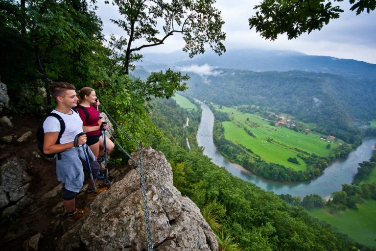 Hikers enjoying the misty view of the Kolpa river meanders from the rock cliff in Bela Krajina.