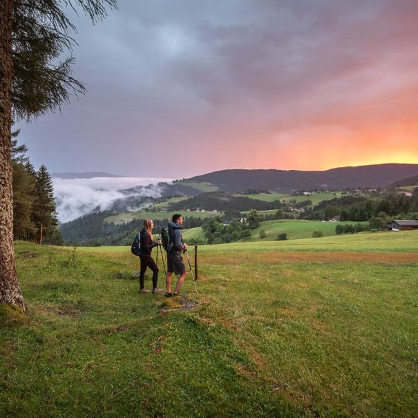 A couple on a walking trip across Pohorje hills enjoying colorful sunset in the countryside of Rogla.