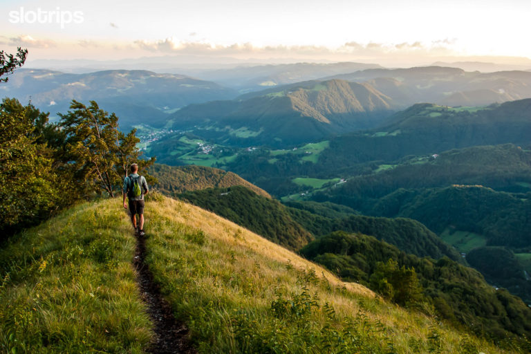 Hiker descending the grassy Blegos mountain ridge in the sunset, surrounded with the wooded Skofja Loka hills.