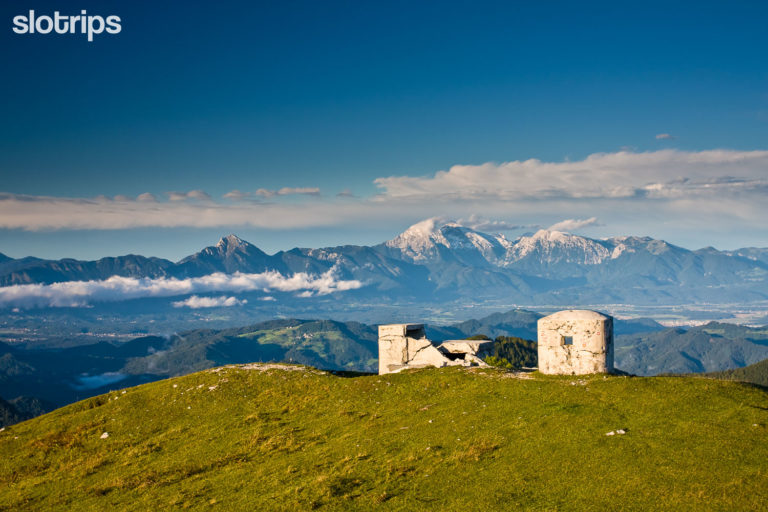 Hiking trip view of the historic world war bunkers on the juicy green ridge of mount Blegos with spectacular Kamnik-Savinja Alps mountain chain background.