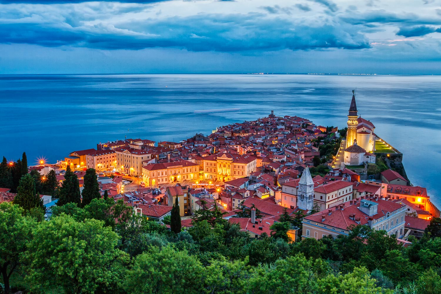 The town of Piran illuminated with street lights, surrounded with heavy clouds and deep blue Adriatic sea, Venice in the background.