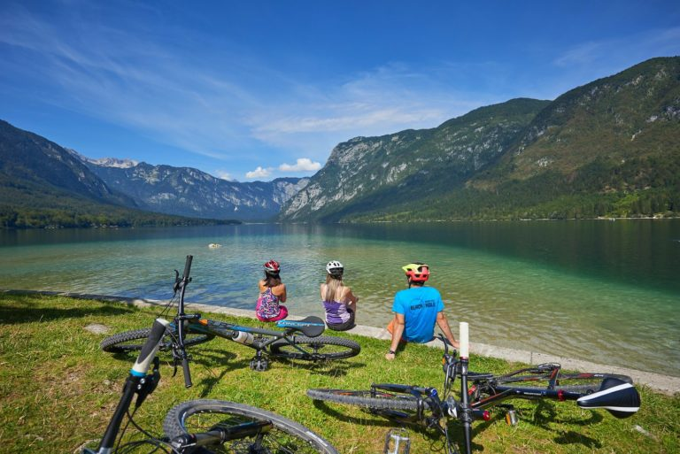 Bikers sitting on a shore of Lake Bohinj staring into distance towards Vogel Ski Resort in Julian Alps, Slovenia