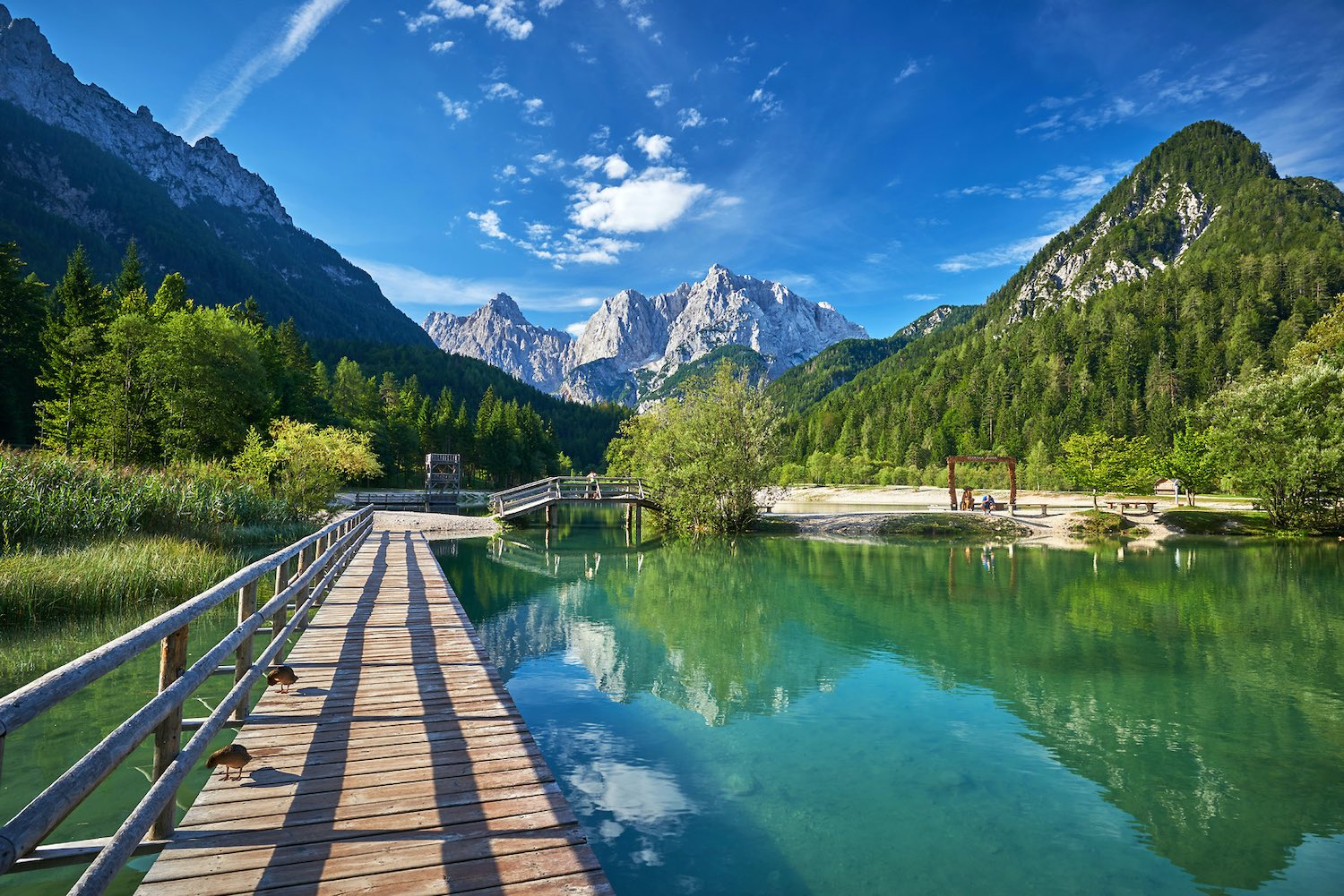 A bridge at Lake Jasna in Kranjska Gora with Mt. Prisojnik and Vrsic Pass in the background, Julian Alps, Slovenia