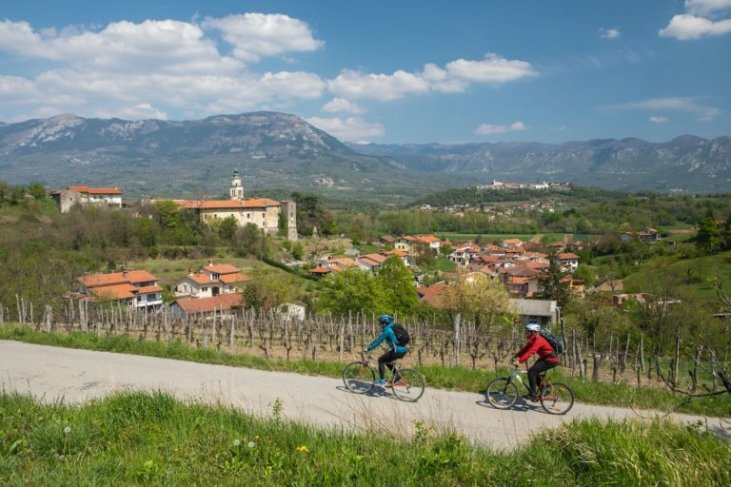 A couple biking through the wine hills in Vipava Valley, Slovenia