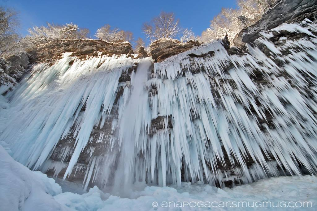 Upwards view of Pericnik waterfall rock face covered with numerous icicles.