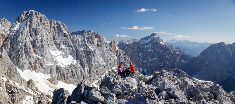 A couple of hikers enjoying a break in the surrounding of the highest mountains of the Julian Alps.