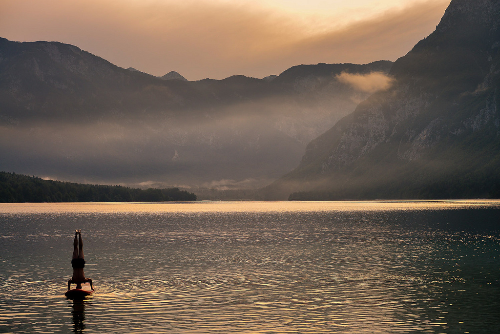 Traveller making headstand on the paddle board on the Bohinj Lake on a steamy evening, with Bohinj mountains backdrop.