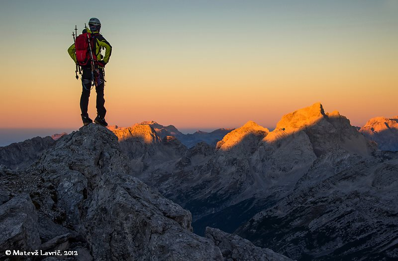 Mountain hiker standing on the tip of the rock edge, admiring orange mount Triglav summit illuminated by the sun setting.
