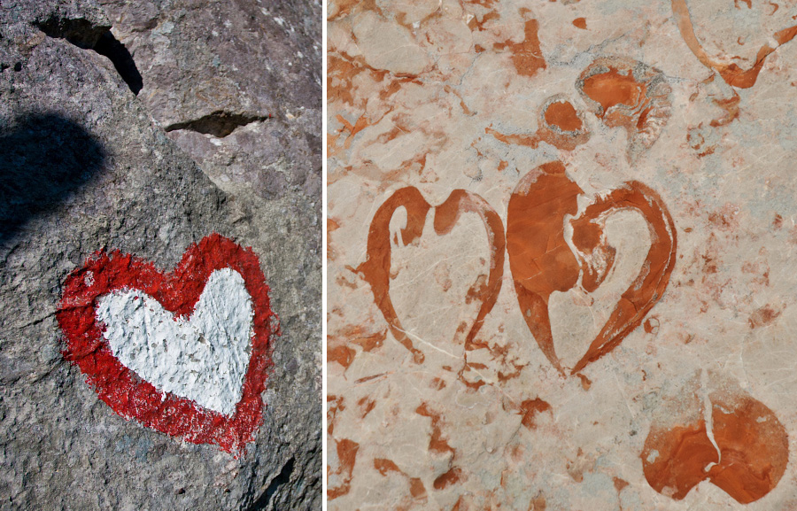 Cute red and white heart shaped Slovenian mountain trail mark and orange heart shape shell fossils on a rock.