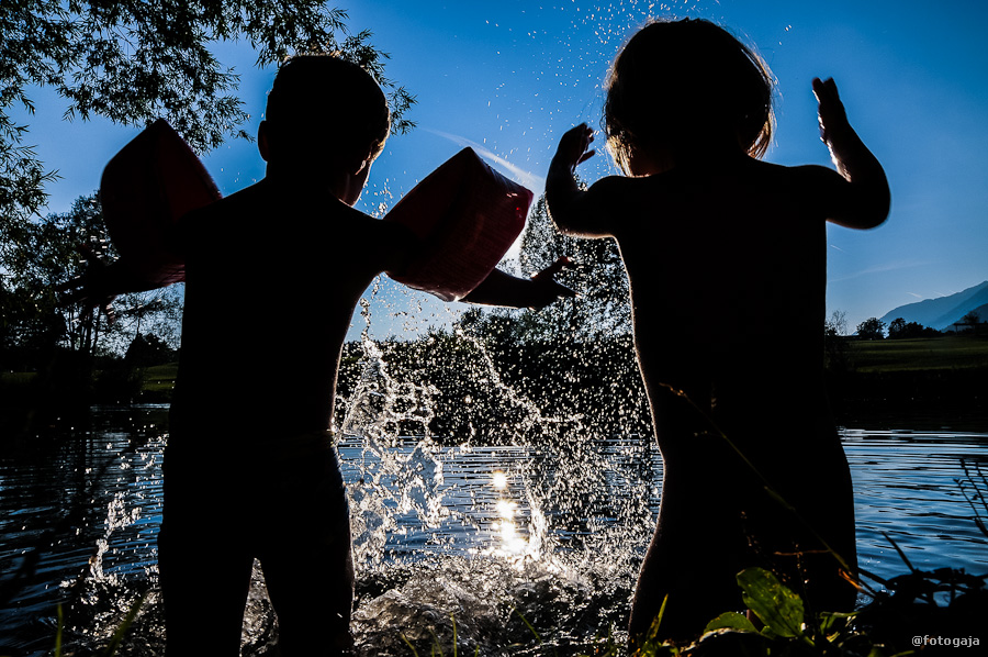 Silhouettes of kids sprinkling water in the Crnava Lake in Preddvor while on a family holiday in Slovenia.