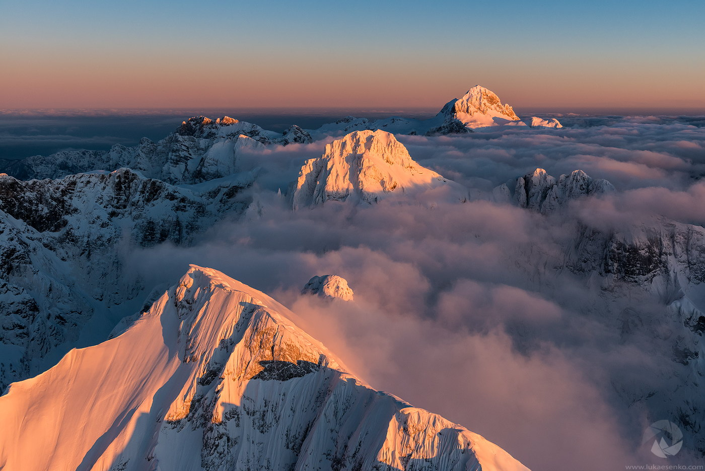 The highest mountains of the Julian Alps peaking out of the fog, colored pink by the sunset, captured from air by Luka Essenko.